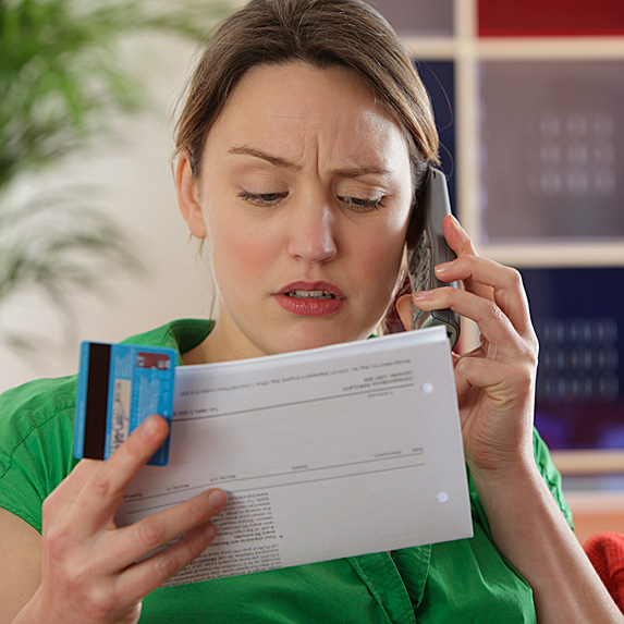 Woman on phone, looking at credit card bill with skeptical look on face