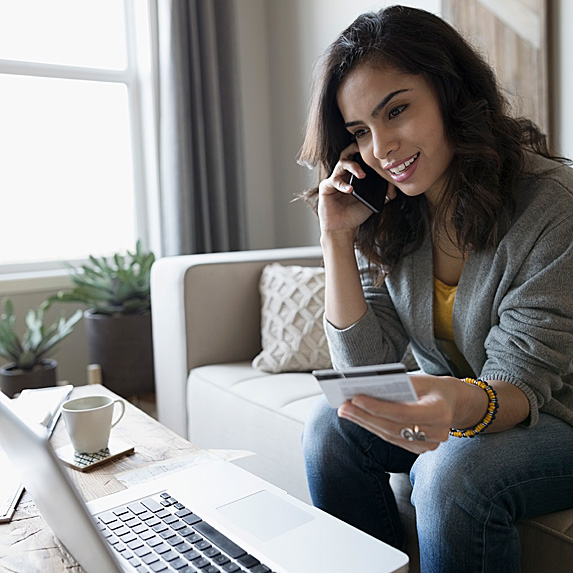 Smiling woman on phone, holding credit card, looking at laptop