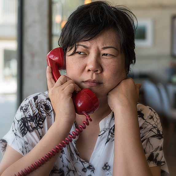 Confused-looking woman using corded phone