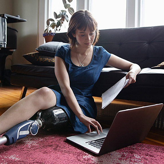 Woman sitting on floor, holding paper while on laptop