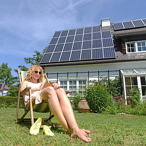 Woman suntanning on lawn chair outside home with solar panels on roof