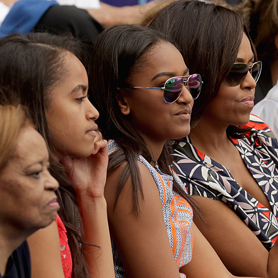 Michelle Obama sitting with her daughters