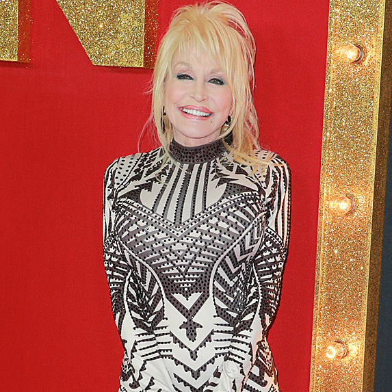 Dolly Parton standing and smiling, dressed up