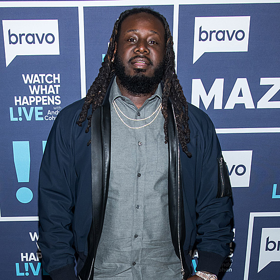 T-Pain standing in front of a backdrop at an event