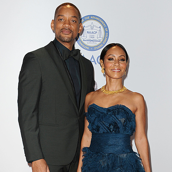 Will Smith and Jada Pinkett-Smith standing at a formal event