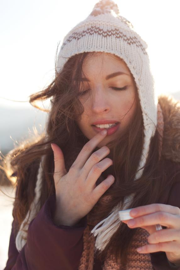 Woman wearing winter layers outdoors applies lip balm