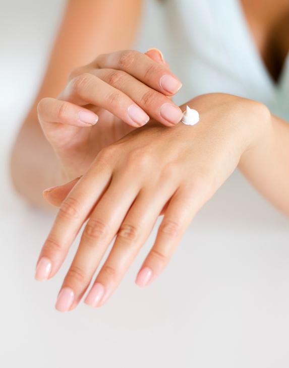 Woman applies moisturizer to her hands
