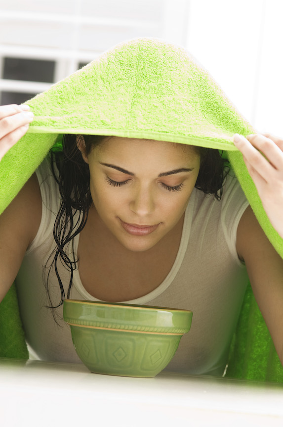 Woman with green towel over her head takes in steam from a green bowl