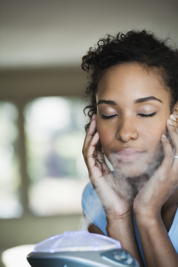Woman sits by a humidifier
