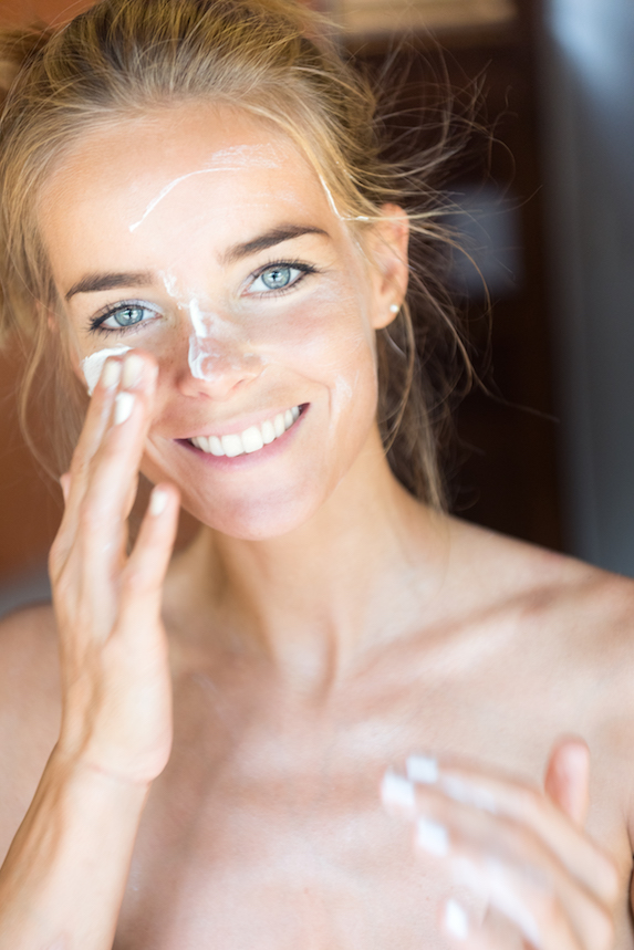 Woman smiles as she applies sunscreen to her face