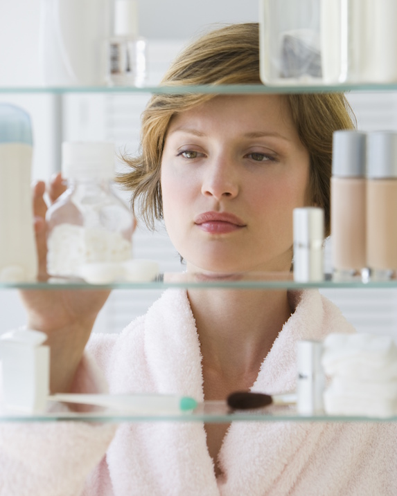 Woman examines beauty products on a shelf in the bathroom