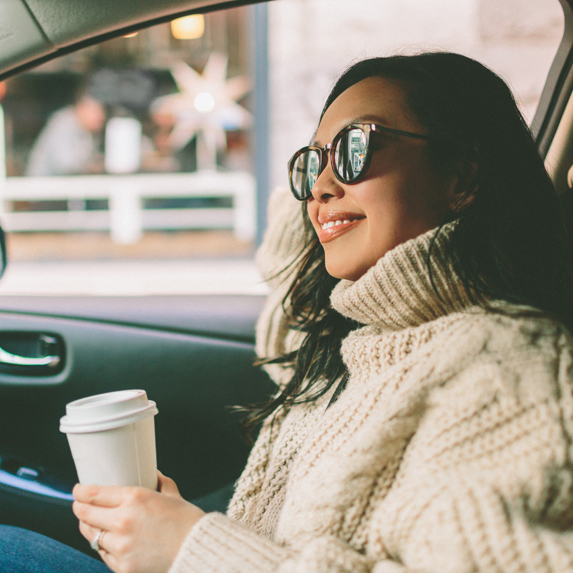a young woman holding a mug of coffee in a car