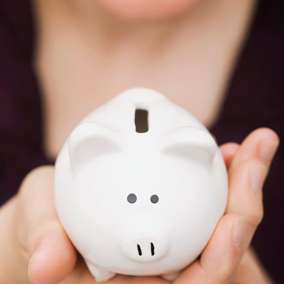 a tiny white piggy bank in the palm of a woman's hand