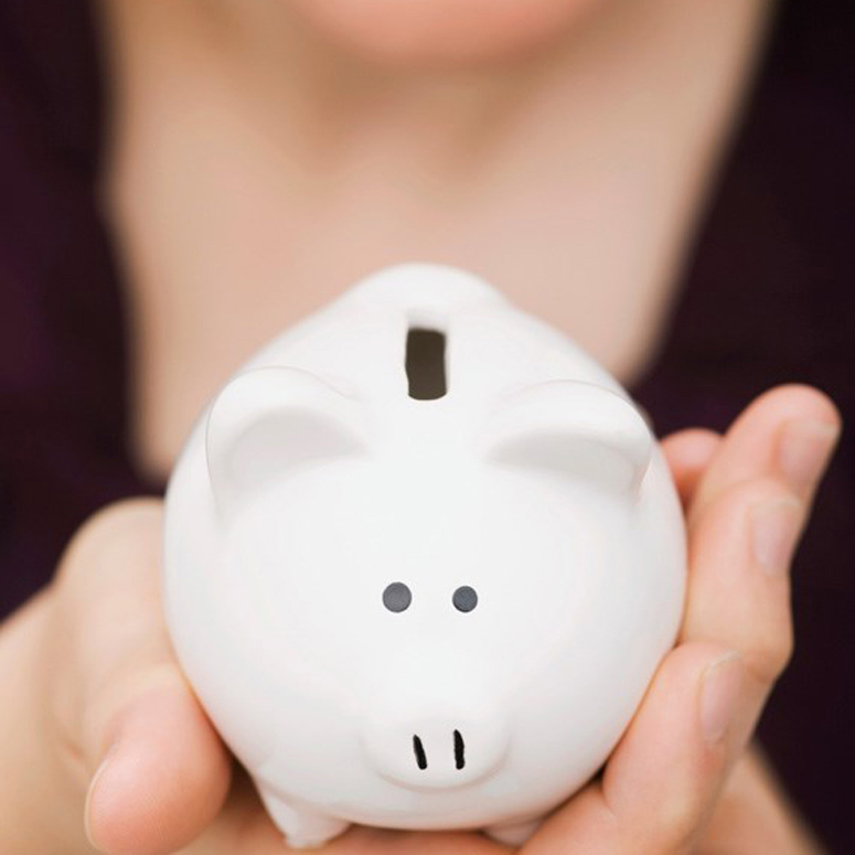 a tiny piggy bank held in the palm of a woman's hand