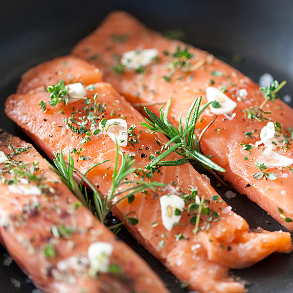 Three filets of salmon garnished with dill and garlic