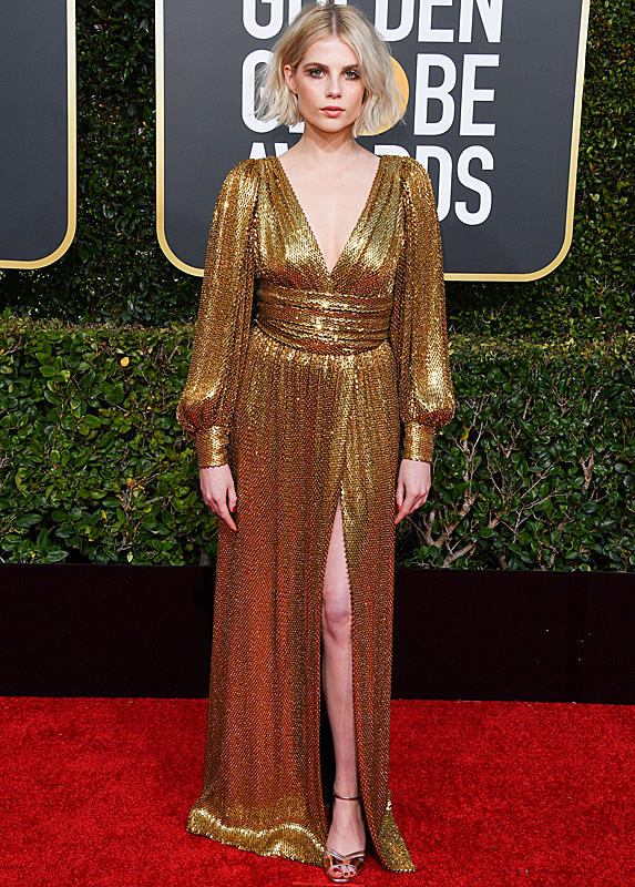 Lucy Boynton in a glittery gold dress with high slit