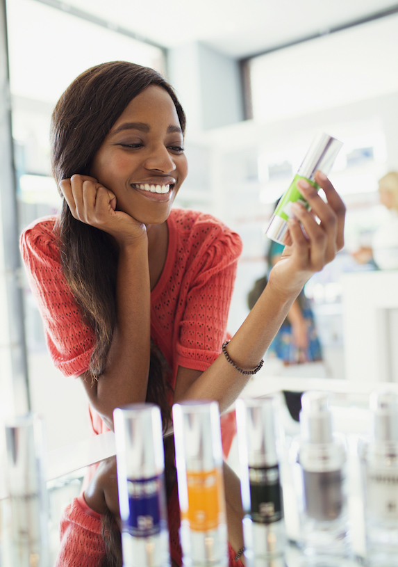 Woman examines beauty product in drugstore