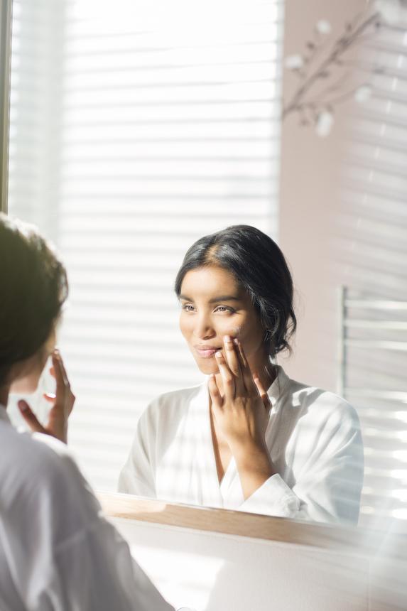 Woman examines her face in bathroom mirror