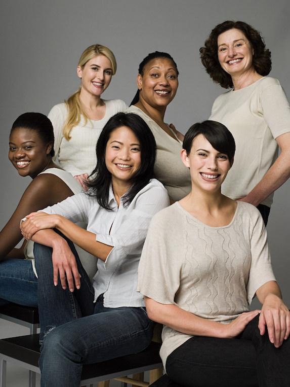 A group of smiling women of various nationalities and ages