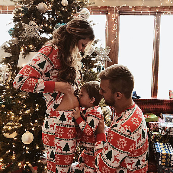 Woman, man and son in matching pajamas, with little boy kissing mom's belly