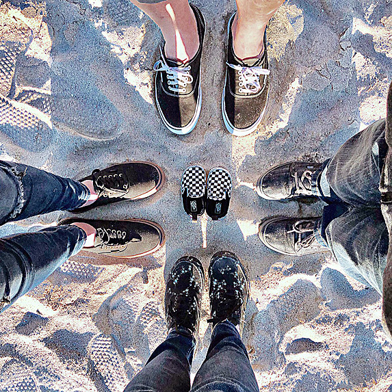 Overview of four pairs of black shoes on sand, with a pair of black baby shoes in the middle