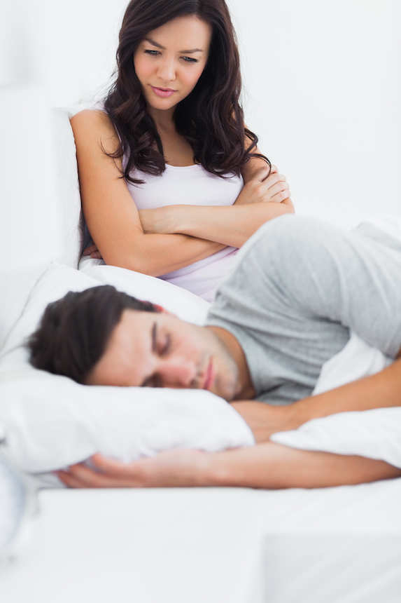 Frustrated woman watches partner sleeping in bed