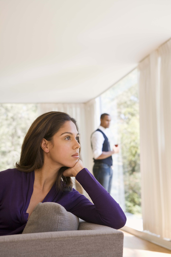 Woman sits on a sofa looking thoughtful as her partner looks on in the background