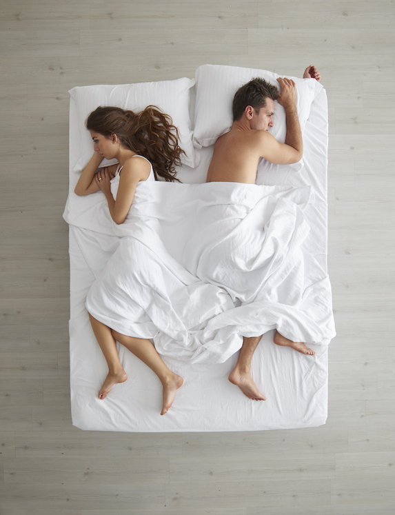 Young couple lie on a mattress, facing away from one another