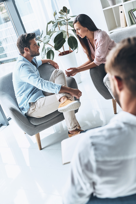 A couple looks frustrated as they argue while in a therapist's office