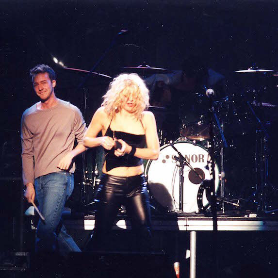 Edward Norton and Courtney Love on stage at a concert