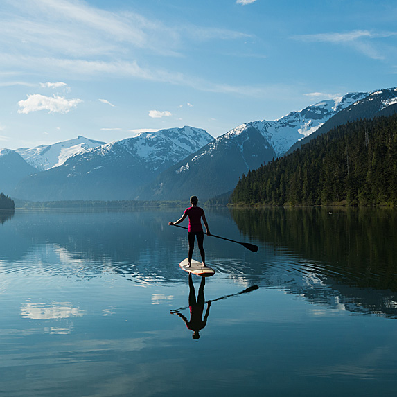Rear view of woman paddleboarding on lake with mountains in front of her