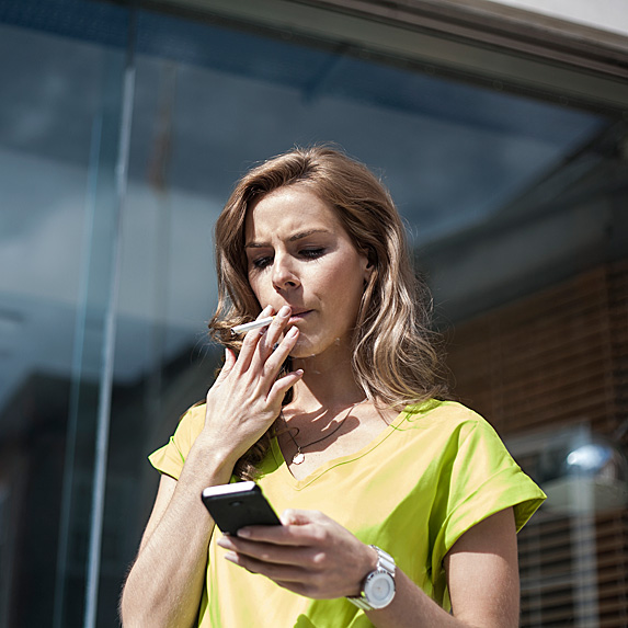 Woman smoking outside while looking at her phone