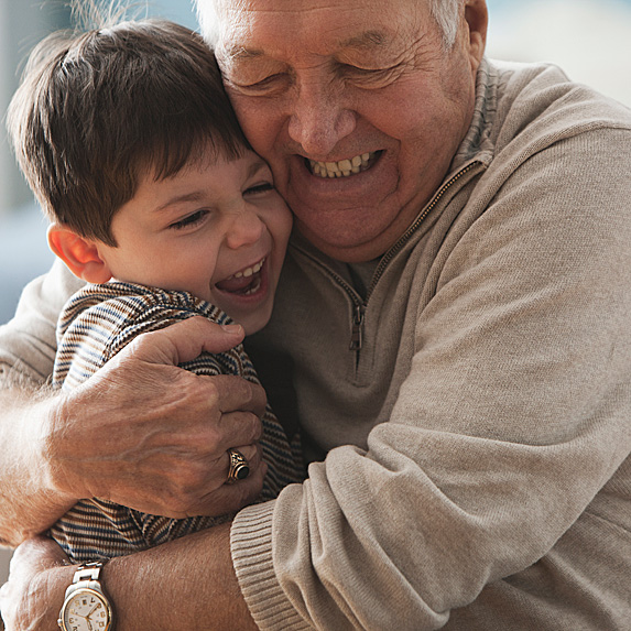 Grandfather hugging grandson hard