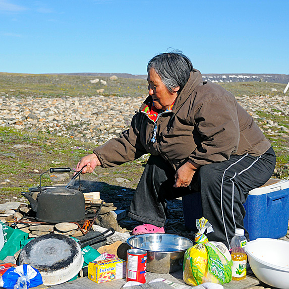 Inuit woman cooking on campfire oven