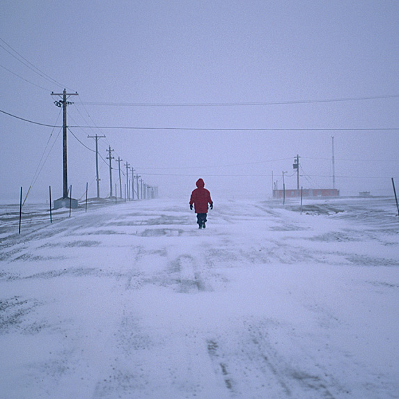 Person in red coat walking down isolated street in snowstorm