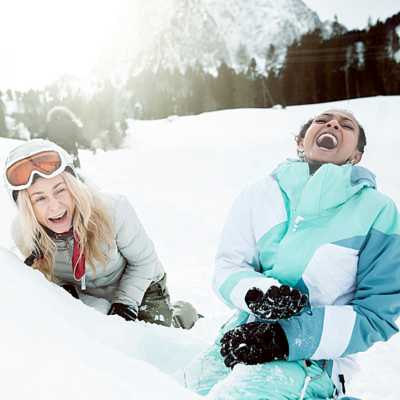 Two women laughing hard in the snow