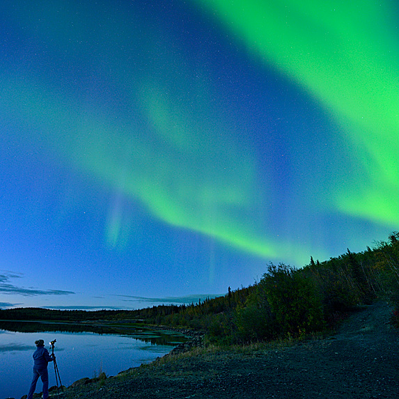Photographer next to lake shooting Aurora Borealis