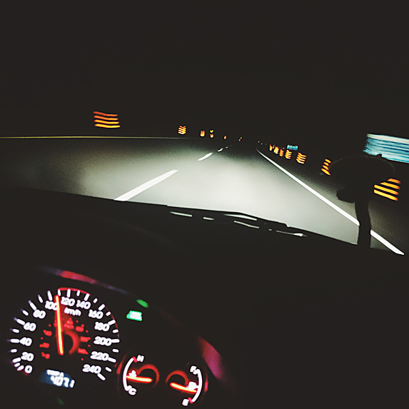 Interior of car showing speedometer and headlight-lit road ahead