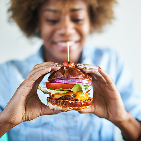 Woman holding a huge, packed burger