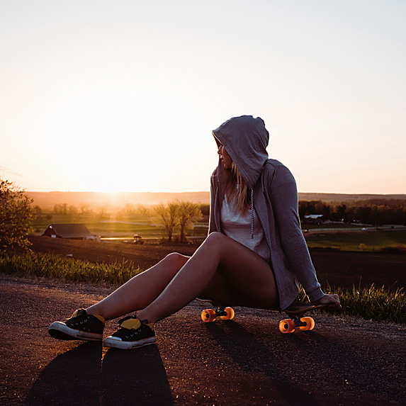 Hoodie-clad young woman sitting on skateboard looking at sunset