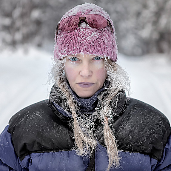 Woman looking frozen and uncomfortable outside in snow