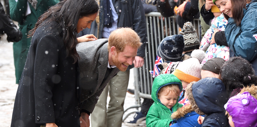 Meghan Markle and Prince Harry greet a group of children