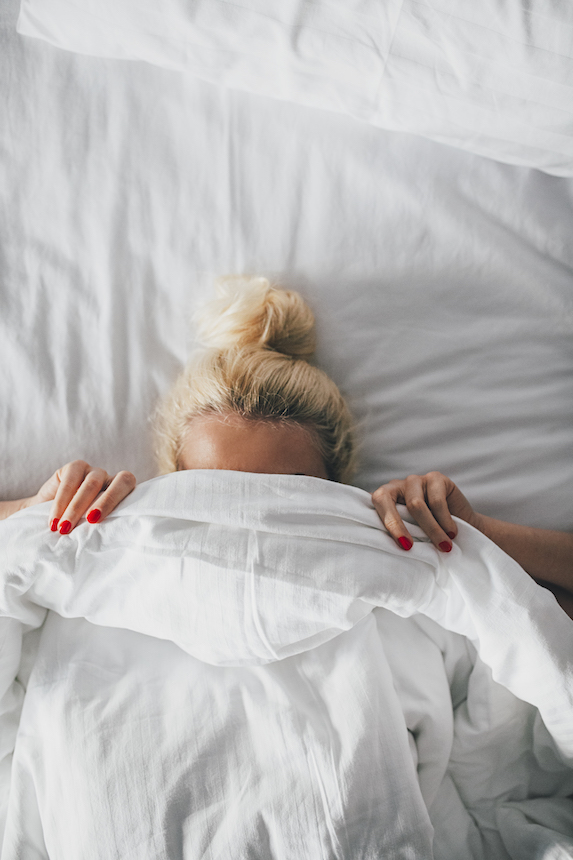 Woman in bed holds the comforter up over her face
