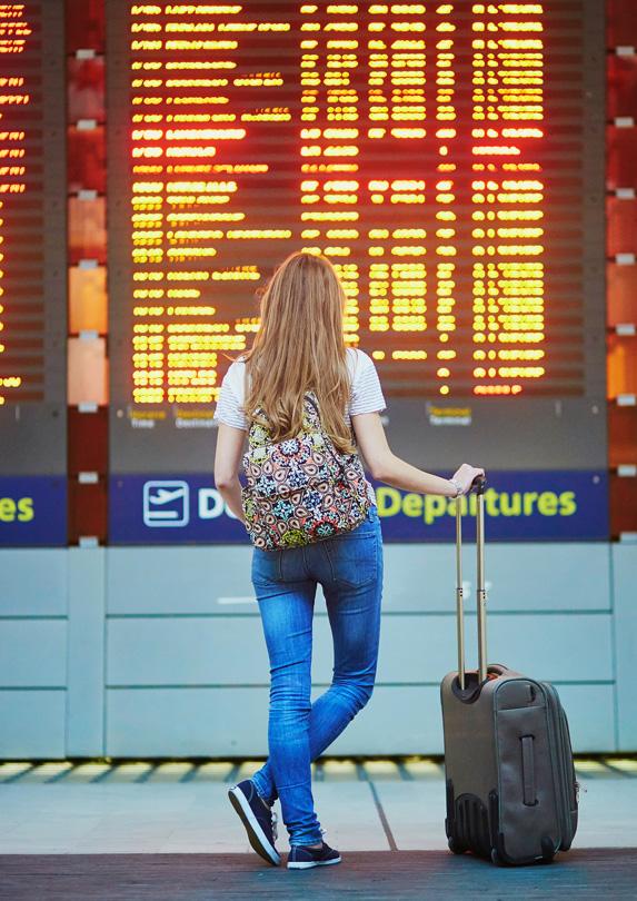 Traveller looking at departure board in airport