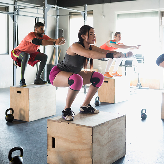 Group of people exercising together performing box jumps