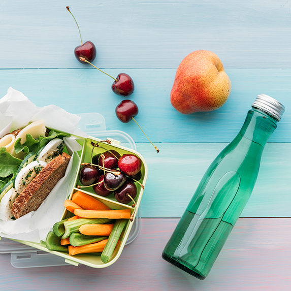 Bottle of water and a sandwich lunch paired with fruits and vegetables