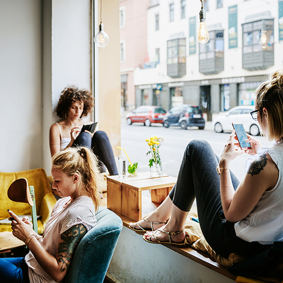 Three women sharing a space while each is looking at their smart phone