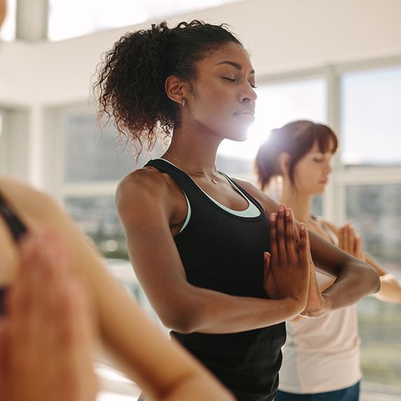 Women practicing in a restorative yoga class.