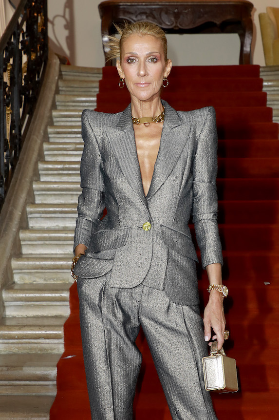Céline Dion in a grey pantsuit with exaggerated shoulder details