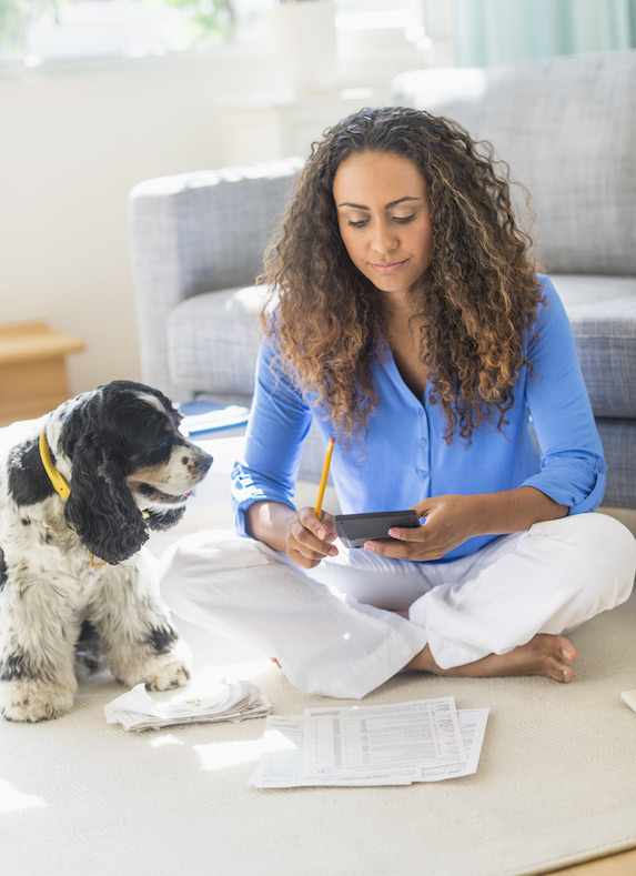 Woman sits on the ground reviewing paperwork with her dog sitting next to her